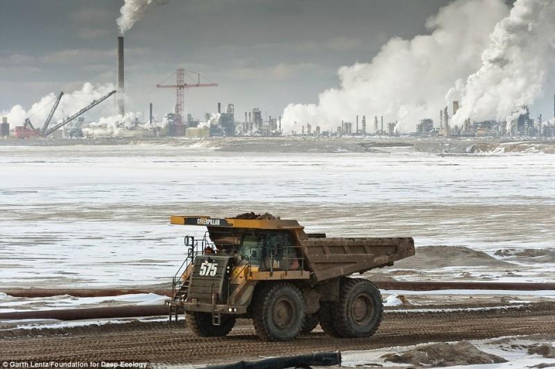 Огромный грузовик везет груды песка на переработку. Нефтеносный песок - источник энергии будущего.